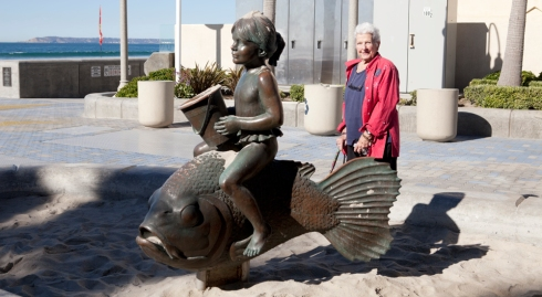 Mother posing with part of a bronze sculpture at Imperial Beach