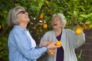 Marion and Lois with backyard orange tree